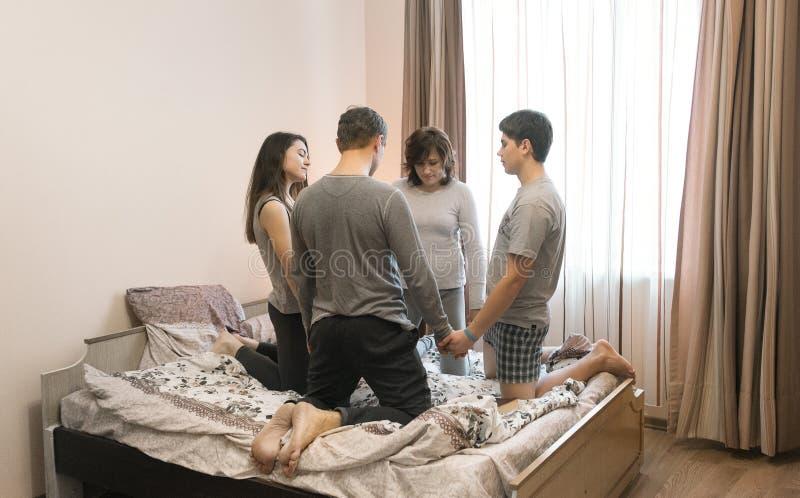 Familj som hemma ber på sängen på början av dagen arkivbilder