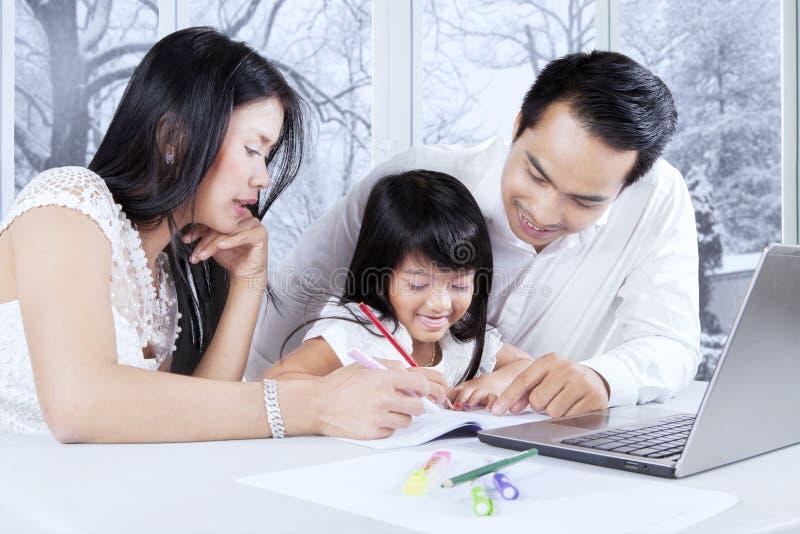Familj som hemma gör schoolwork royaltyfri fotografi