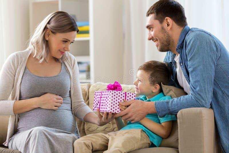 Familj som hemma ger gåva till den gravida modern royaltyfria bilder