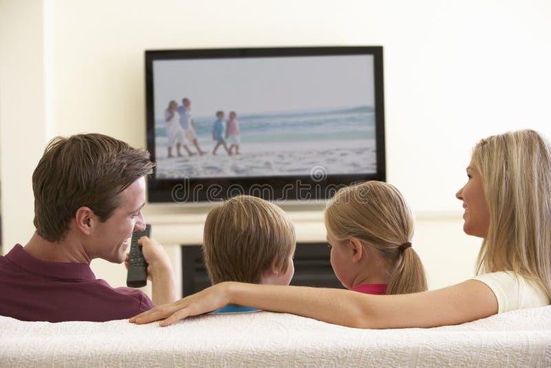 Familj som hemma håller ögonen på Widescreen TV arkivbild