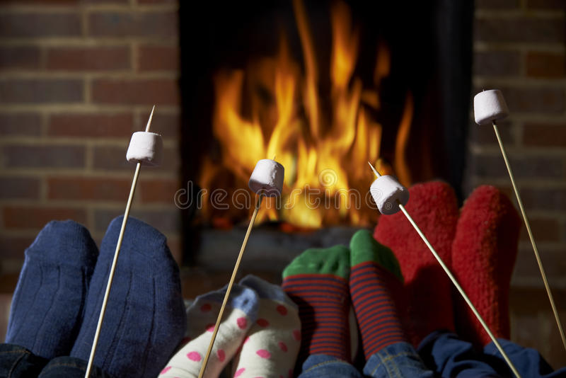 Familj som hemma rostar marshmallower vid öppen brand arkivfoton