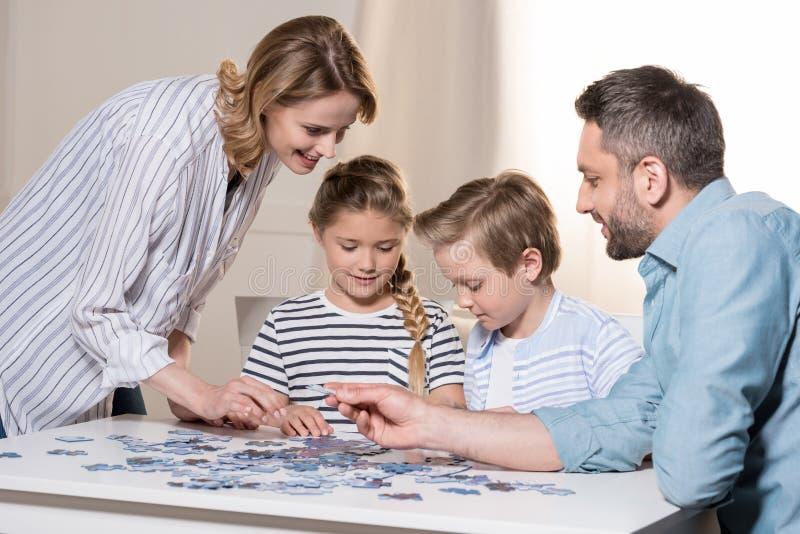 Familj som hemma spelar med pusslet på tabellen tillsammans arkivfoton