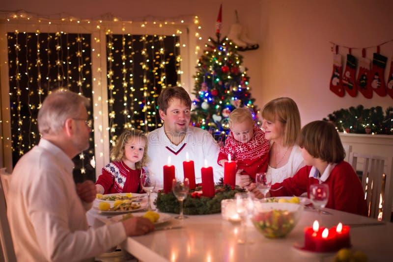 Familj som hemma tycker om julmatställen arkivbilder