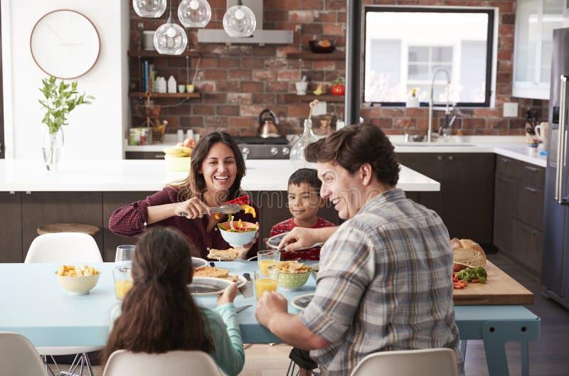 Familj som hemma tycker om mål runt om tabellen tillsammans royaltyfri fotografi