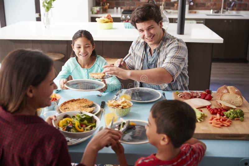 Familj som hemma tycker om mål runt om tabellen tillsammans royaltyfri foto