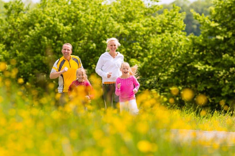 Familj som joggar i ängen för kondition arkivbild