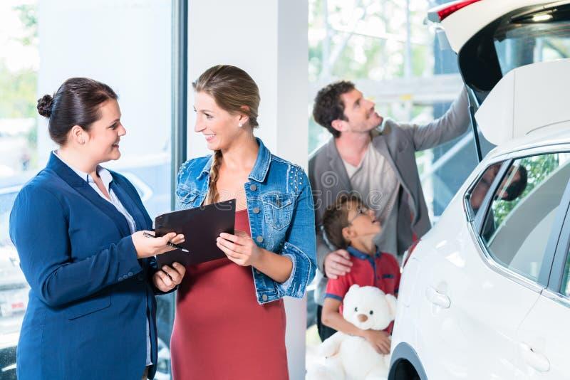 Familj som köper den nya bilen i visningslokal för auto återförsäljare arkivfoto