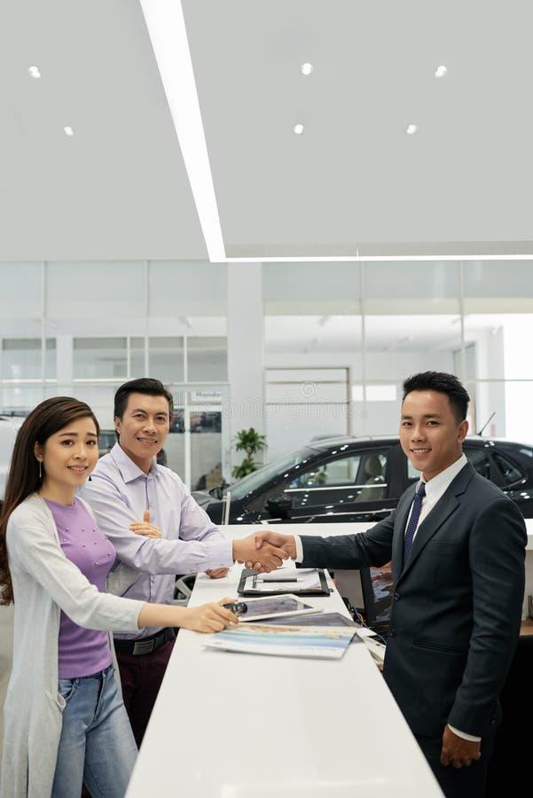 Familj som köper den nya bilen arkivbild