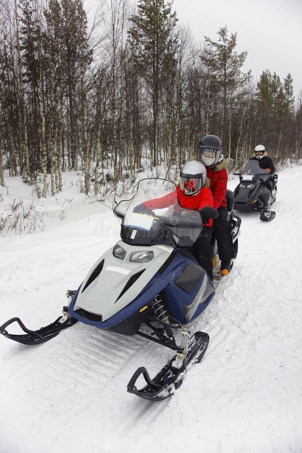 Familj som kör snövessla i Ruka av Lapland arkivbilder