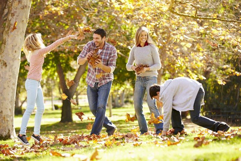 Familj som kastar Autumn Leaves In The Air arkivfoto