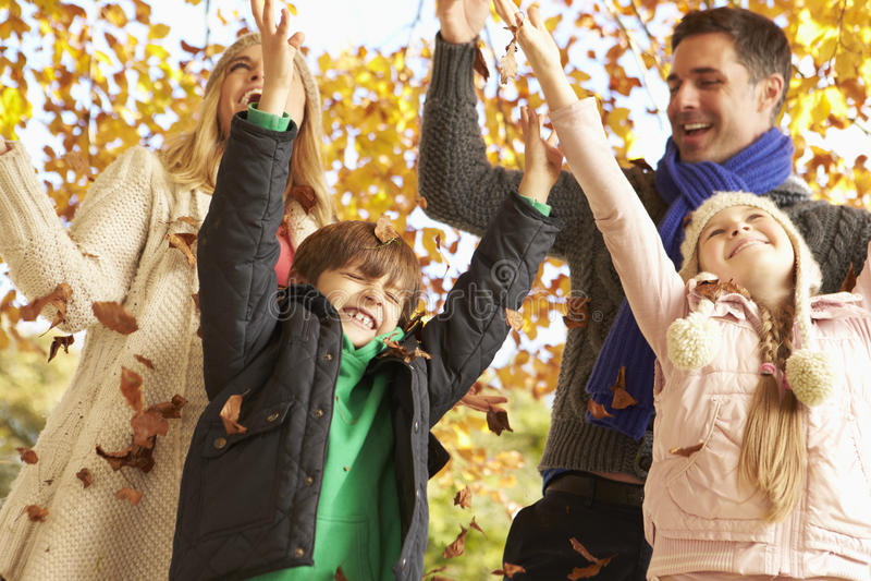 Familj som kastar sidor i Autumn Garden fotografering för bildbyråer