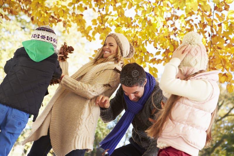 Familj som kastar sidor i Autumn Garden arkivfoton