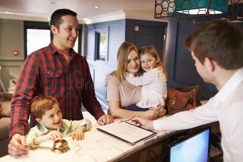 Familj som in kontrollerar på hotellmottagandeskrivbordet arkivbilder