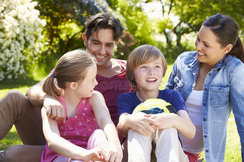 Familj som kopplar av i sommarträdgård royaltyfria foton