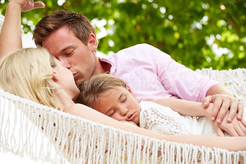 Familj som kopplar av i strandhängmatta royaltyfri fotografi