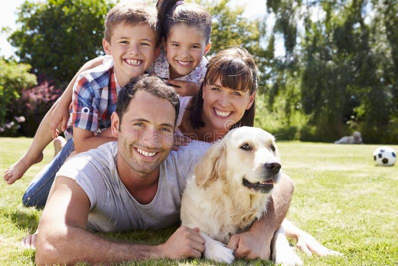 Familj som kopplar av i trädgård med den älsklings- hunden royaltyfri bild