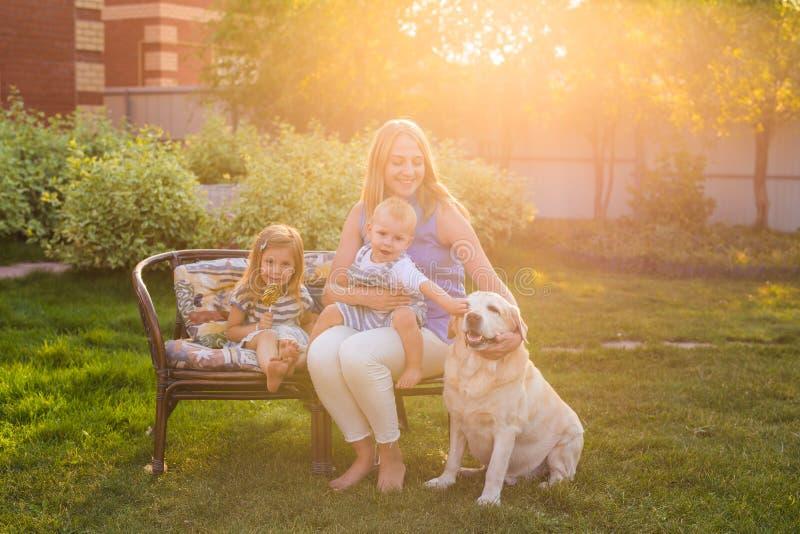 Familj som kopplar av i trädgård med den älsklings- hunden royaltyfri foto