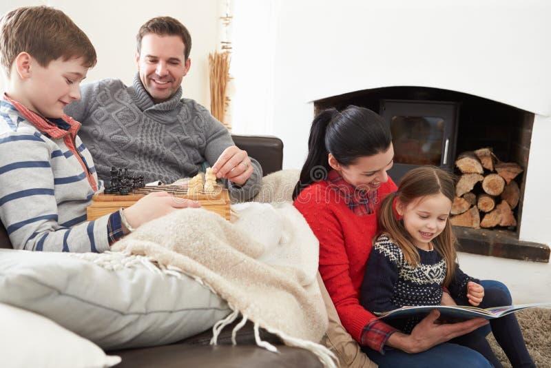 Familj som kopplar av inomhus att spela schack och läseboken royaltyfria foton