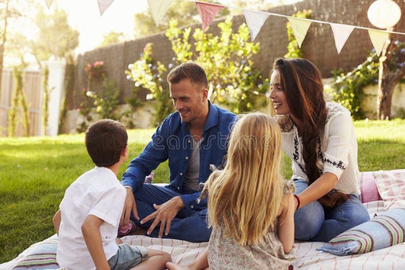 Familj som kopplar av på filten i trädgård royaltyfri bild