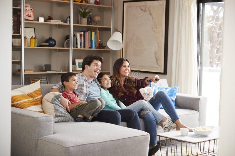 Familj som kopplar av på Sofa At Home Watching Television arkivbilder