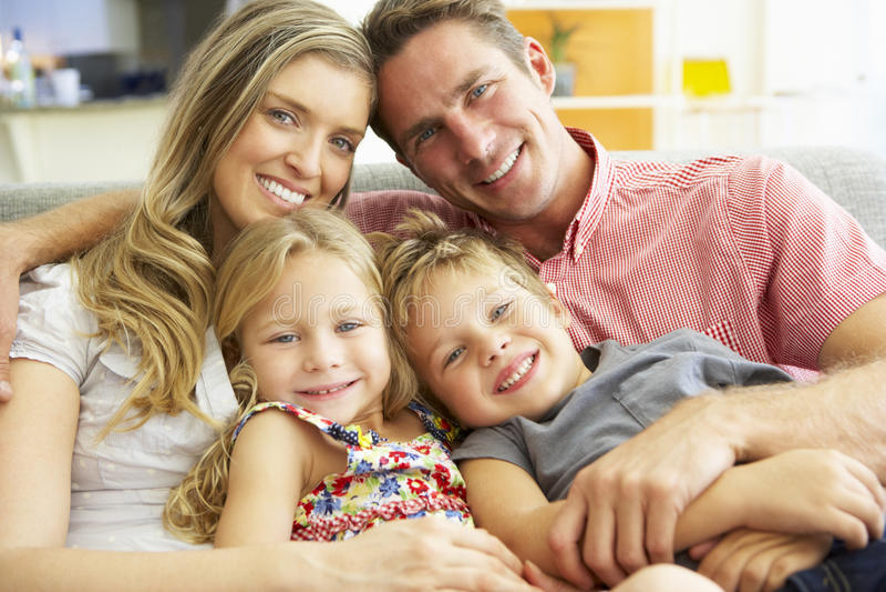 Familj som kopplar av på Sofa Together royaltyfria foton