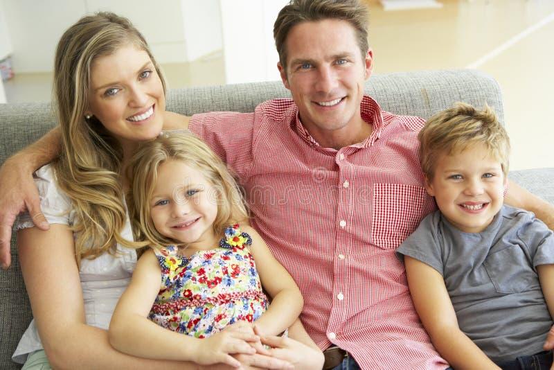 Familj som kopplar av på Sofa Together royaltyfria bilder