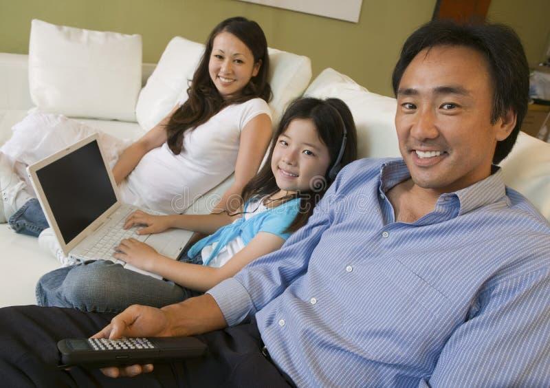 Familj som kopplar av på soffan i vardagsrumdotter med bärbar datorståenden royaltyfria bilder