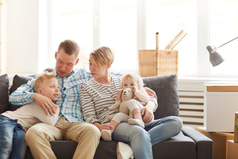 Familj som kopplar av p? soffan fotografering för bildbyråer
