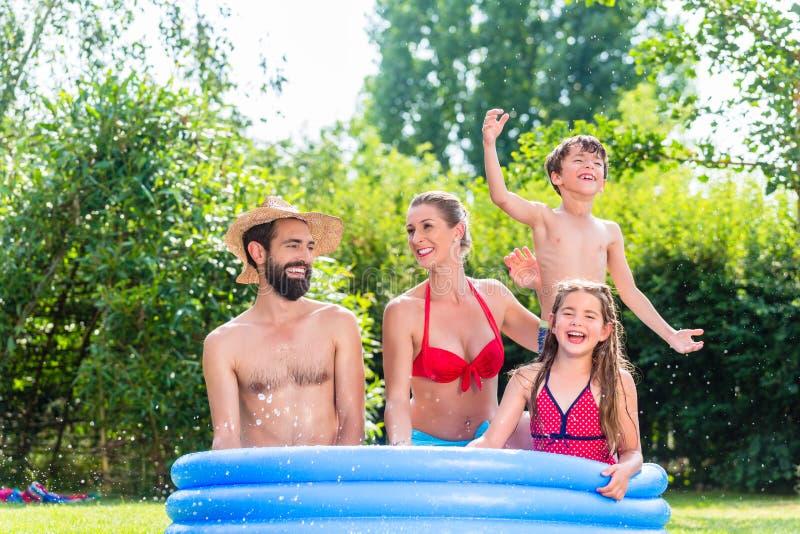 Familj som kyler ner att plaska vatten i trädgårds- pöl arkivfoto