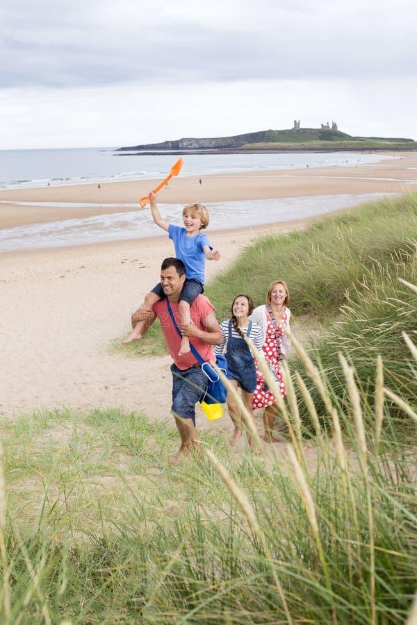 Familj som lämnar stranden royaltyfria bilder
