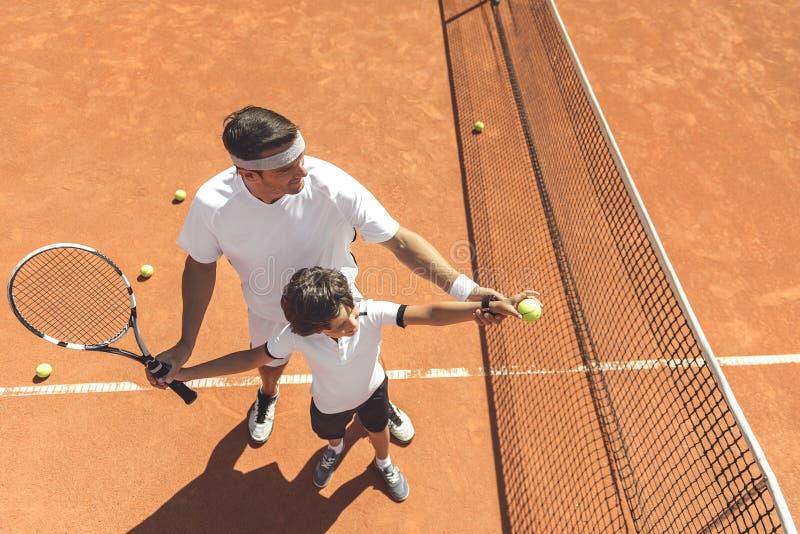 Familj som lär att spela tennis royaltyfri foto