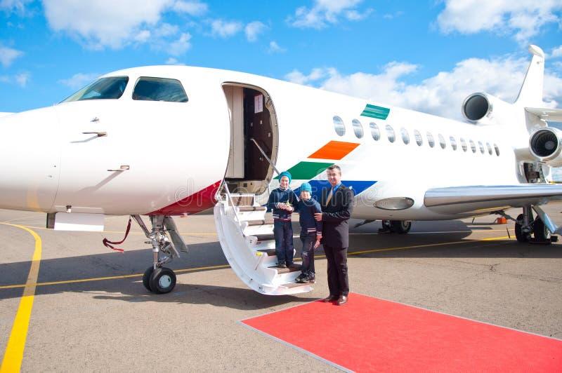 Familj som löper med det kommersiella flygplan royaltyfri fotografi