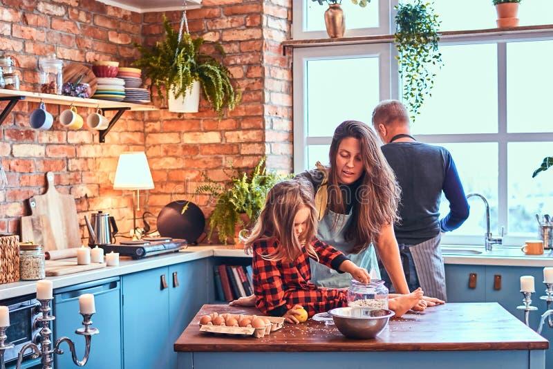 Familj som lagar mat tillsammans frukosten i vindstilkök royaltyfri fotografi