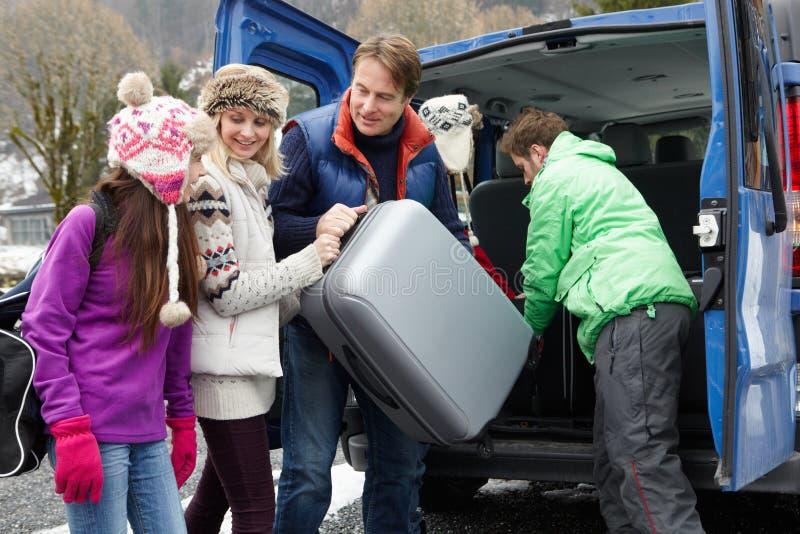 Familj som lastar av bagage från överföringsskåpbilen royaltyfri fotografi