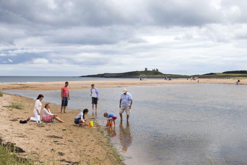 Familj som leker på stranden arkivbilder