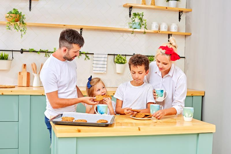 Familj som ler ha frukosten i k?k p? den soliga dagen royaltyfri foto
