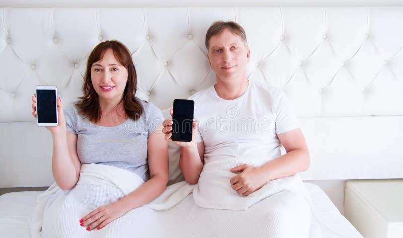 Familj som ligger i sovrummet och rymmer mobiltelefoner fotografering för bildbyråer