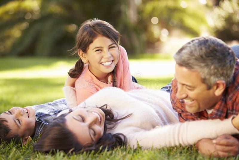 Familj som ligger på gräs i bygd arkivbild