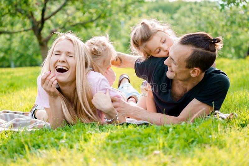 Familj som ligger på gräs i bygd arkivfoto