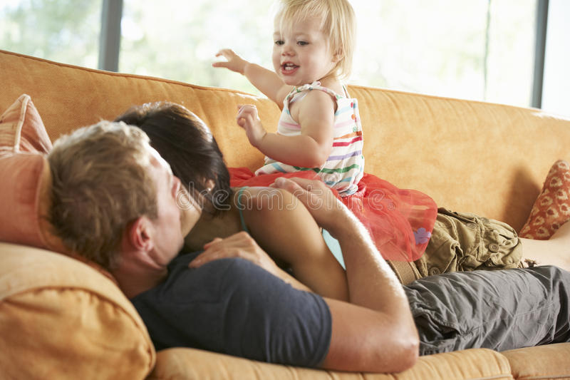 Familj som ligger på Sofa At Home royaltyfri foto