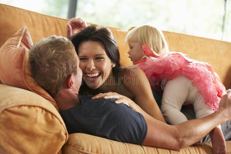 Familj som ligger på Sofa At Home royaltyfri bild