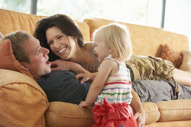 Familj som ligger på Sofa At Home royaltyfria bilder