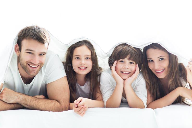 Familj som ligger under duntäcket arkivfoton