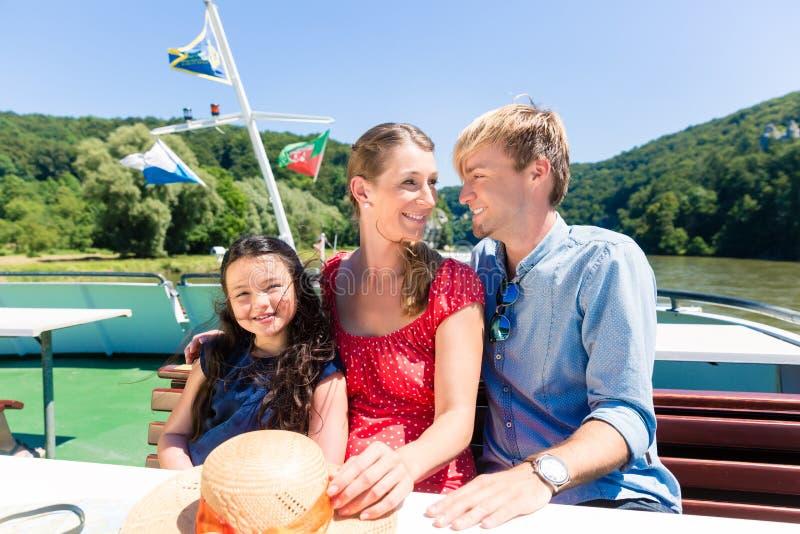 Familj som lyckligt sitter på fartyget på flodkryssning i sommar royaltyfri fotografi