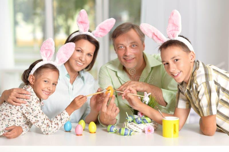Familj som målar easter ägg arkivfoto
