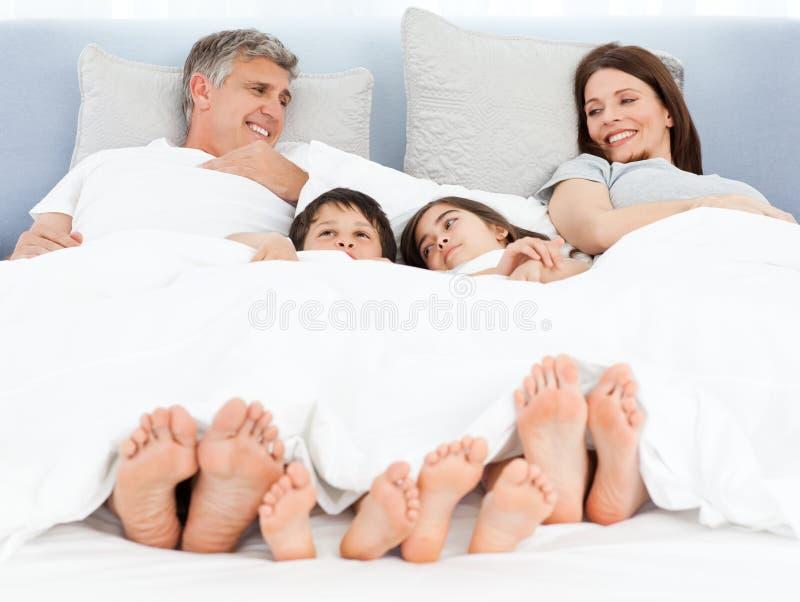 Familj som ner ligger i deras underlag arkivfoton