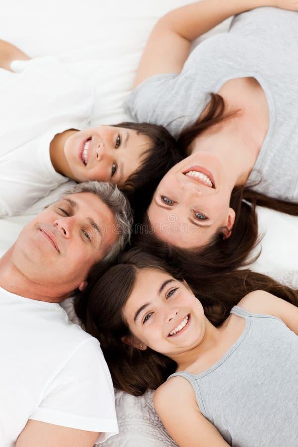 Familj som ner ligger på deras underlag royaltyfri bild