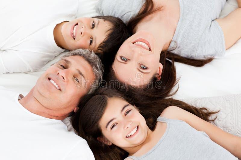 Familj som ner ligger på deras underlag arkivbilder