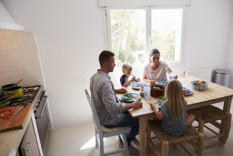 Familj som ner sitter för att äta lunch på köksbordet arkivbild