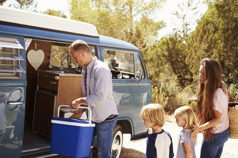 Familj som packar upp deras campareskåpbil för en semester för vägtur royaltyfri fotografi